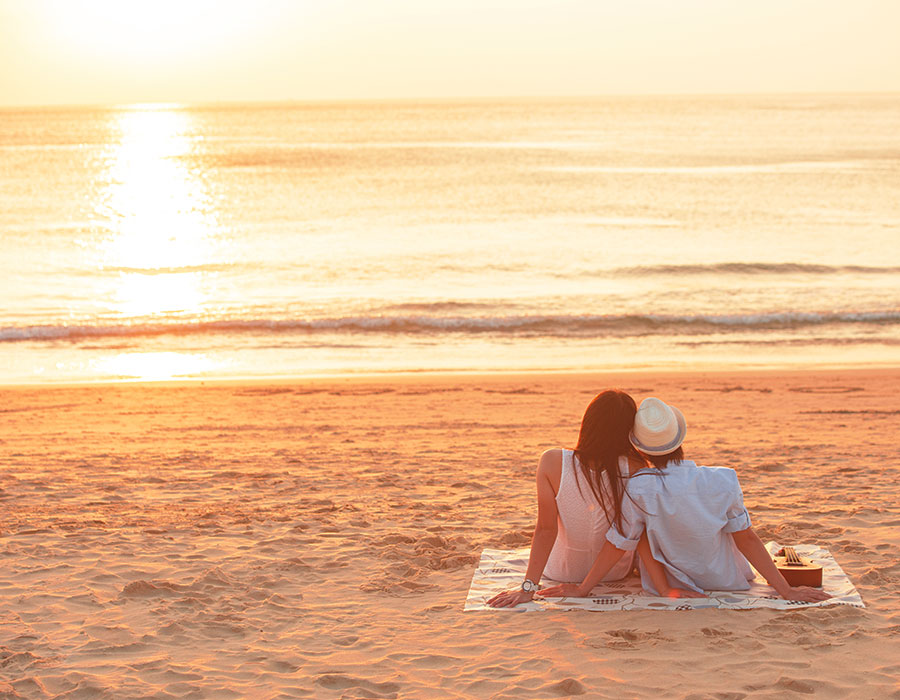A couple enjoying a sunset on the beach